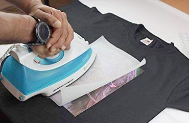 Best Iron On Transfer Paper Have you ever wanted to print your own custom designs on your t-shirt? Well, the truth is many people actually do this very thing. You may have no doubt noticed t-shirts with unique designs on people. But when you want to buy them, you will have a hard time finding them on the market. The reason is, the person did not actually buy it, but rather printed the design on his t-shirt himself. This is a great way to add a touch of flair and personality to your outfit. And you can do it on any plain t-shirt you own. To do that, you need a printer, the t-shirt you want to print, and most importantly a transfer paper. Transfer papers are unique printer papers made to transfer designs from paper to fabric. There are many types of transfer papers out there. But the easiest one to use is perhaps an iron on transfer paper. You do not need a heat press to operate it. Simply place it over your t-shirt and roll an ordinary hand iron over it. In this article, we will give you an in-depth look at some of the best iron on transfer papers available on the market. And also help you figure out which one you want for the best possible results. So, without further ado, let us dive in. What is Iron On Transfer Paper? Before we dive deeper, let us take a moment to discuss what exactly is an iron on transfer paper. Well, it is exactly what it sounds like; a transfer paper that you iron on! They are also commonly referred to as T-shirt papers. If you break it down, it is essentially a type of heat transfer paper. But instead of having to use a heat press machine, you can easily transfer the design printed on the paper to the t-shirt using a hand iron. Typically, you need a printer to use it though as you need a way to get your design printed on paper first. After that, you position the paper on the t-shirt where you want to paste the design and press down on it using your hand iron. After a couple of minutes, you will have your design printed on the t-shirt perfectl